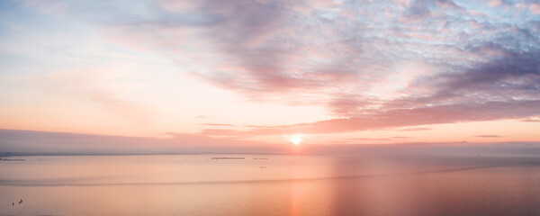 Calm pink colored sea and sky at sunset