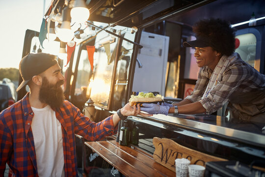 afro-american female employee gives with care sandwich to young hipster male customer