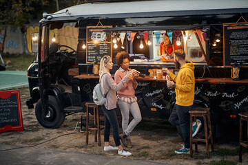 group of people socializing while eating outdoor in front of modified truck for fast food