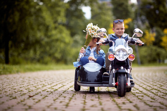 Happy little boy and a girl driving in a toy motocycle