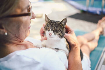 Happy smiling senior elderly woman in glasses relaxing in summer garden outdoors hugging domestic tabby cat. Retired old people and animals pets concept