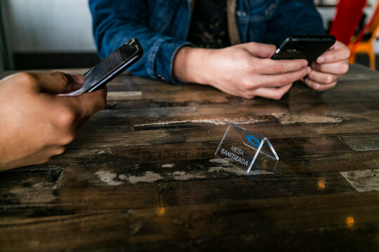 """""""Sanitized Table"""" Sign over a table. Hands with cellphone over a table in a restaurant."""