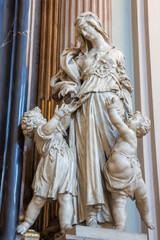 VIENNA. AUSRIA - JULY 27, 2013: The statue of cardinal virtue Charity from baroque church Maria Treu. Church was build between years 1698 bis 1719 by plans of architect Lukas von Hildebrandt