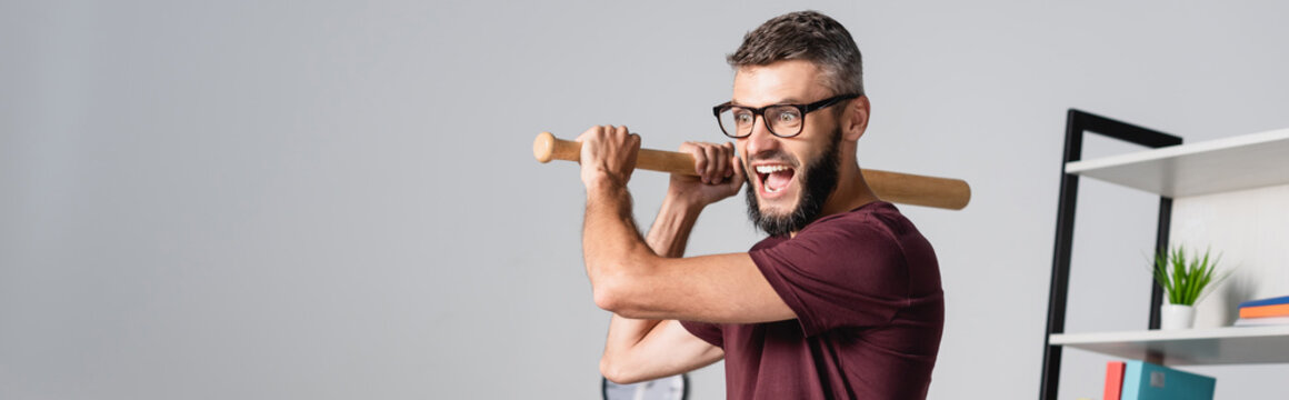 Stressed businessman holding baseball bat while screaming in office, banner
