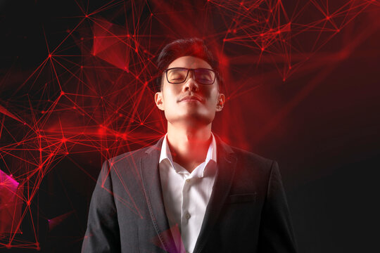 Man and digital technology, Asian CEO business man standing thinking in dark red futuristic artificial intelligence background.