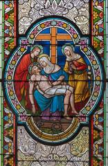 VIENNA, AUSTIRA - OCTOBER 22, 2020: The Deposition - Pieta on the stained glass in in church Pfarrkirche Kaisermühlen by workroom Tiroler Glasmalerei-Anstalt from end of 19. cent..
