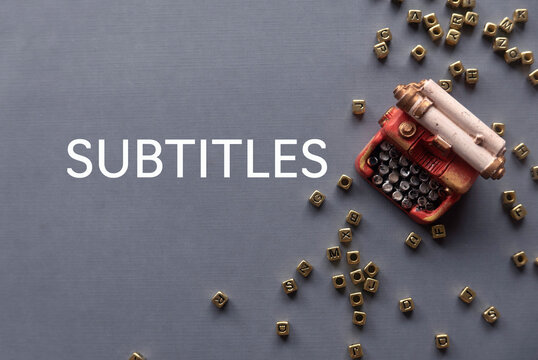 Top view of toys typewriter and gold alphabet beads on grey background written with Subtitles.