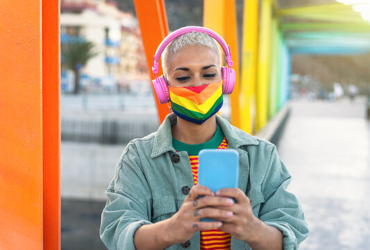 Young woman wearing gay pride mask using mobile smartphone while listening to music with wireless headphones outdoor - Gender equality and technology concept