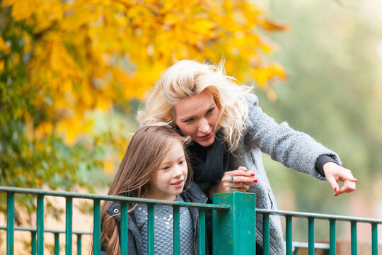 Mother and daughter at park in autumn in London - Happy mom and girl wearing warm clothes on a funny day out together - fall season lifestyle image