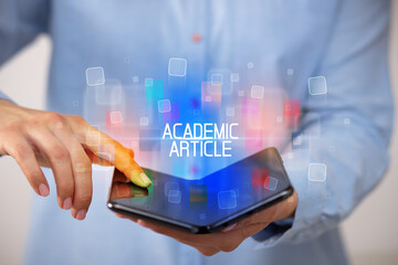 Young man holding a foldable smartphone with ACADEMIC ARTICLE inscription, educational concept