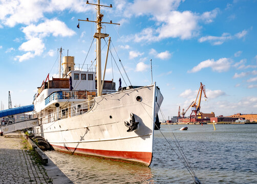 A vintage grey passenger ship docked in a harbor with a dockyard with cranes visible in the background.