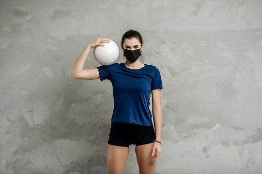 Young woman protective face mask with volleyball ball isolated on grey background. Protective masks against virus infection. Vintage color filter