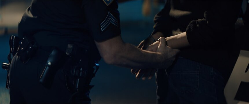 CLOSE UP Police officer handcuffs a suspect near police car, African-American Black criminal. Lights flashing in the background. Shot with anamorphic lens