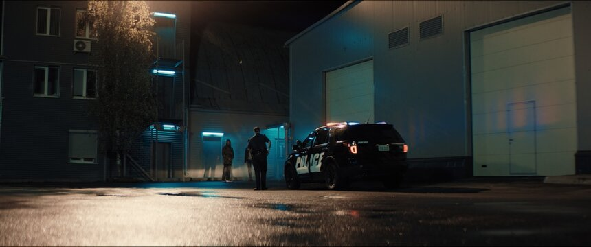 WIDE Police officer exiting a car and approaching two multi-ethnic males suspects near industrial buildings at night. Shot with anamorphic lens