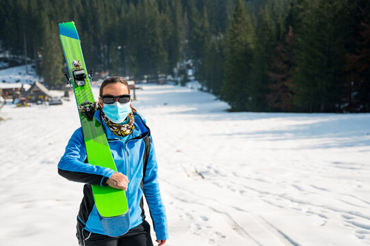 Female skier posing with a pait of skis wearing protective face mask.