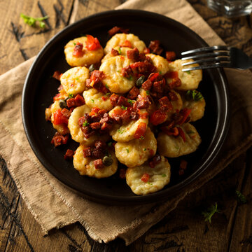 Homemade gnocchi with fried sausage and tomato