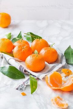 Tangerine, mandarine or clementine on white marble background.