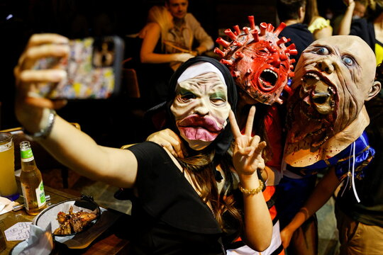 A man wears a face mask depicting coronavirus as he celebrates Halloween at Lan Kwai Fong, a popular nightlife destination in Central, following the coronavirus disease (COVID-19) outbreak, in Hong Kong