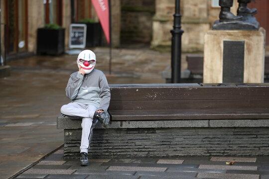 A man wears a Halloween mask in Durham