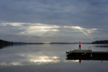 the sun's rays make their way through the clouds above the lake, a female silhouette on a wooden...