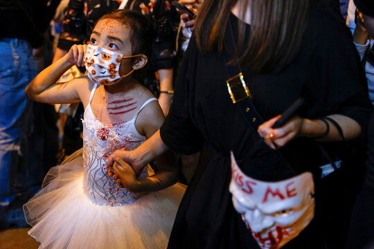 A child wears a protective mask and a costume as she celebrates Halloween at Lan Kwai Fong, a popular nightlife destination in Central, following the coronavirus disease (COVID-19) outbreak, in Hong Kong