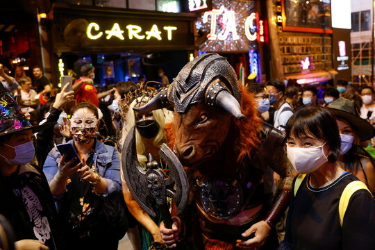 People wear protective masks and costumes celebrating Halloween at Lan Kwai Fong, a popular nightlife destination in Central, following the coronavirus disease (COVID-19) outbreak, in Hong Kong