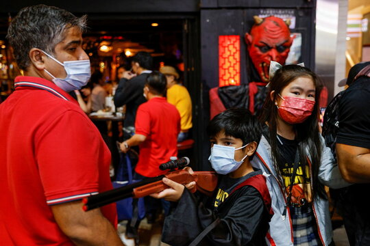 A child wears a protective mask holding a toy gun as he celebrates Halloween at Lan Kwai Fong, a popular nightlife destination in Central, following the coronavirus disease (COVID-19) outbreak, in Hong Kong