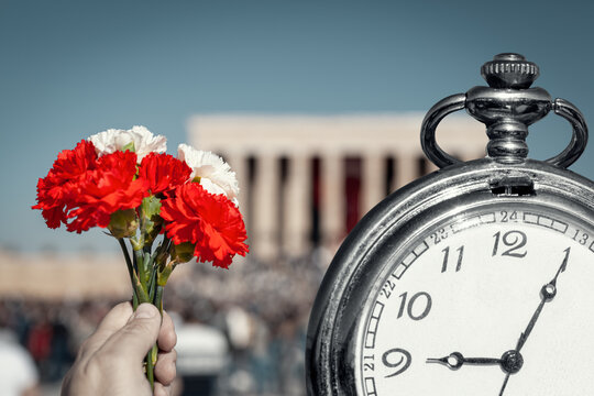 Hand holding red and white cloves next to big pocket watch in front of blurry Anitkabir mausoleum in November 10.  Old pocket watch showing time 9:05 AM, hour of the death of Ataturk.