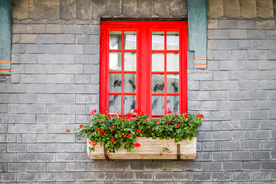 Red window decorated with red flowers on the brick wall of the old half-timbered house in Honfleur, France.