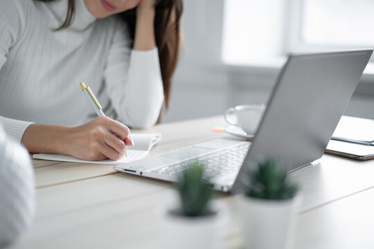 Young woman in troubled sweater sits table in front of laptop and writes in workbook.