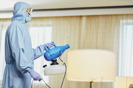 Man in blue protective suit holding disinfectant and standing in the room