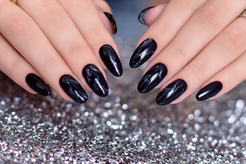 Beautiful female hands with fashion manicure nails, black gel polish, on glitter background