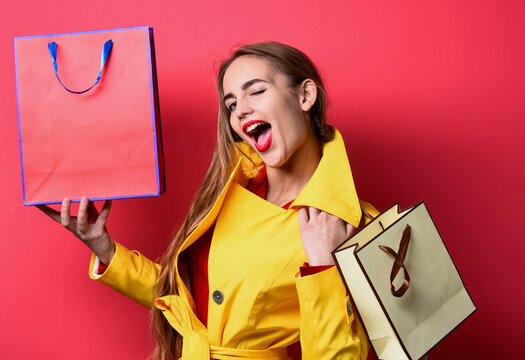 winking woman in yellow coat hold shopping bags, cyber monday