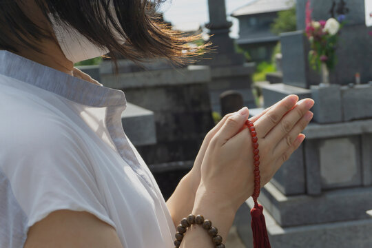 The woman who wore a mask for the infection prevention prays. we photographed it in a Japanese graveyard. 感染予防のマスクをした女性が祈る、お参りする。日本の墓地で撮影しました