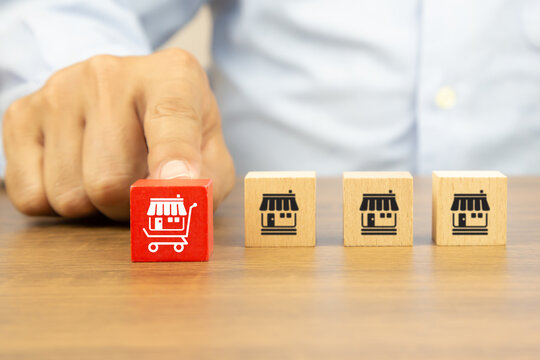 Close-up hand chooses cube wooden toy blocks stack with franchise business store icon in the shopping cart. Concepts of online e-marketplace or e-commerce franchising to growth.