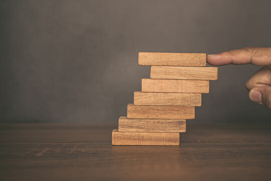 Close-up finger pushing wood block tower stacked in stair step with caution to prevent collapse or crash concepts of financial risk management and strategic planning.