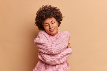 Pretty dark skinned curly woman embraces herself and closes eyes feels comfort in soft warm knitted sweater enjoys home tenderness tilts head poses against beige background. Self love concept