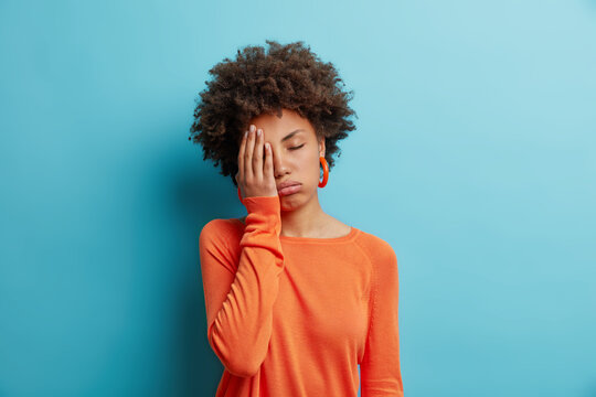 Exhausted unhappy woman makes face palm and sighs from tiredness has sleepy expression fed up of working without rest wears orange jumper in one color with earrings. Upset depressed female model