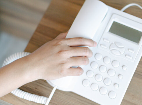 Closeup woman hand holding telephone receiver and dialing a phone number on white landline telephone.