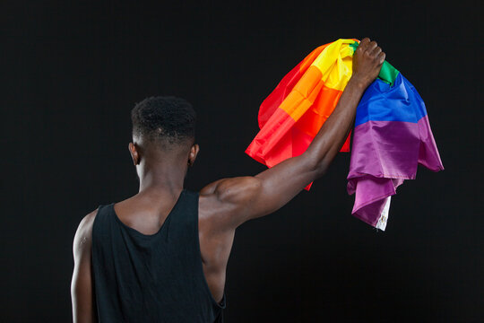 Back view of young african american man holding a rainbow flag in a raised fist isolated on black background. Concept of The LGBT community, minority rights, protection of human rights