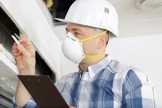 man inspecting a derelict property wearing a dust mask