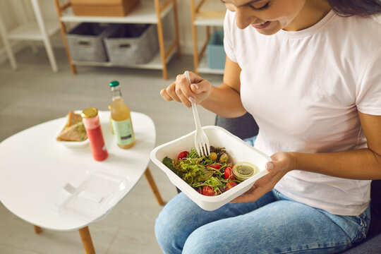 Happy young woman having lunch at home and eating veggie salad from plastic container