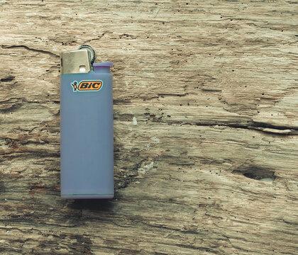 Bic purple lighter on wooden background, Arona 01/11/2020