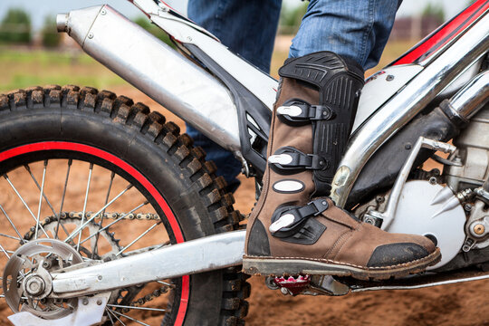Close up view at rider's motocross boot standing on peg of dirt motorcycle. Safety apparel for riding