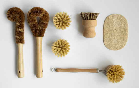 Set of brushes for eco-cleaning the home, washing dishes and surfaces without chemicals on a gray surface. Zero waste kitchen cleaning concept. Eco friendly natural cleaning bamboo dish brushes.