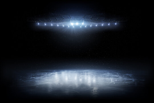 Background. Beautiful empty winter background and empty ice rink with lights. Spotlight shines on the rink. Bright lighting with spotlights. Isolated in black