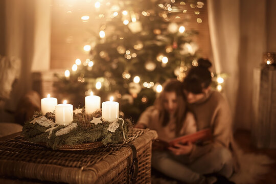 Child sits with mother in front of the Christmas tree and read a book together and look forward to Christmas, advent wreath