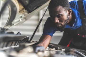 Black male mechanic repairs car in  garage. Car maintenance and auto service garage concept.