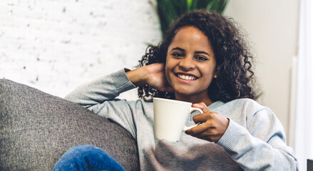 Portrait of smiling happy african american black woman relaxing drinking and looking at cup of hot coffee or tea.Girl felling enjoy having breakfast in holiday morning vacation on bed at home