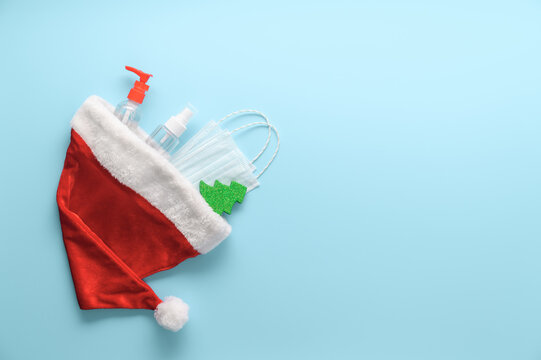 New normal christmas concept. Top view of medical masks, sanitizer bottles, Santa hat and Christmas decorations on pastel blue background. Minimal composition. Copy space, flat lay